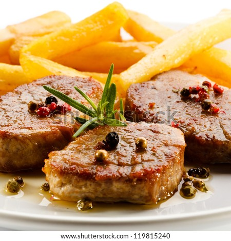 Grilled steaks with French fries - stock photo