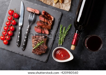 Grilled striploin sliced steak and red wine over stone table. Top view - stock photo
