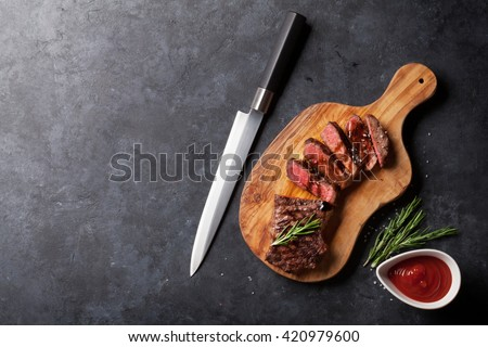 Grilled striploin sliced steak on cutting board over stone table. Top view with copy space - stock photo