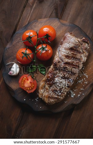Grilled striploin steak with tomatoes, rustic wooden setting, top view