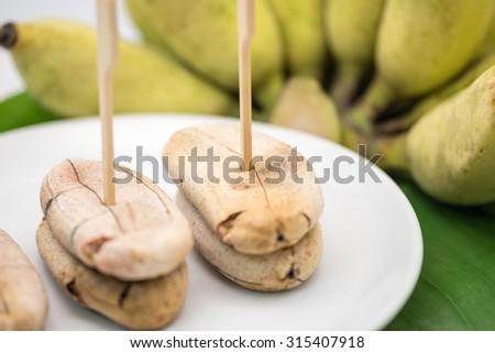 Grilled sweet banana on white ceramic plate on banana leaf for local Thai dessert background - stock photo