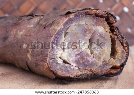 Grilled sweet potatoes on wood board and wooden background
