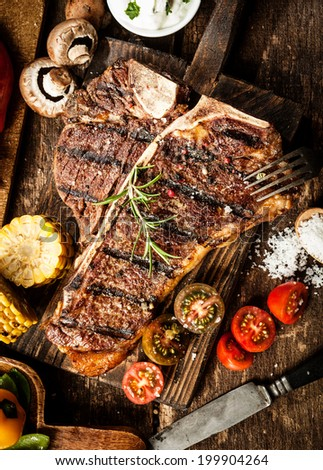 Grilled t-bone or porterhouse steak seasoned with rosemary in a rustic kitchen on a wooden board with tomatoes, corn, mushrooms and salt, overhead view - stock photo