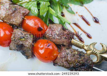 Grilled tenderloin beef kebabs with cherry tomato and potatoes served on a white plate on a wooden table in a restaurant