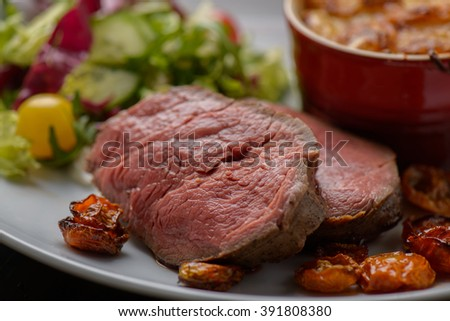 Grilled tenderloin with potatoes in the background - stock photo