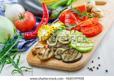 Grilled tomato, corn, eggplant, mushroom, bell pepper, marrow and onion on a table. Healthy prepared food with ingredients.