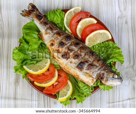 Grilled trout barbeque served lemon, tomato and salad leaves