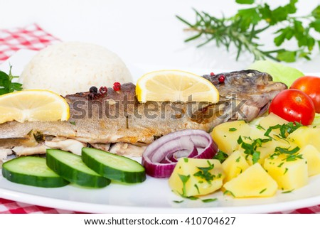 Grilled trout barbeque served with rice, potato, cucumber, tomato, onion and lemon