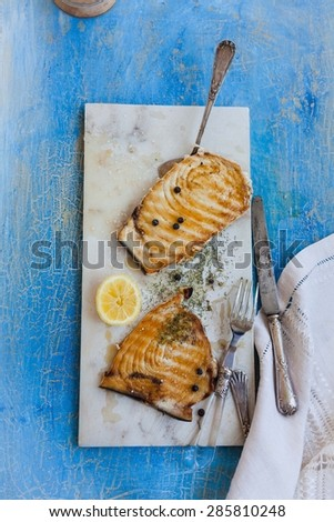 Grilled tuna steak served on marble table over on blue rustic table with kitchen tools and linen napkin. Rustic style. - stock photo