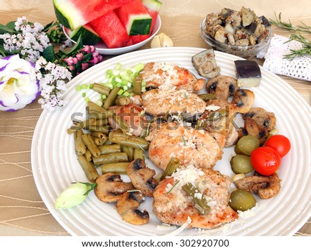 Grilled turkey fillet with grated cheese,green beans(snap beans),mushrooms and eggplants.Pickles and cherry tomato for garnish.Served with flowers and fruit.Mediterranean healthy food. Selective focus - stock photo