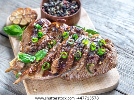 Grilled turkey with green scallion on the wooden board - stock photo