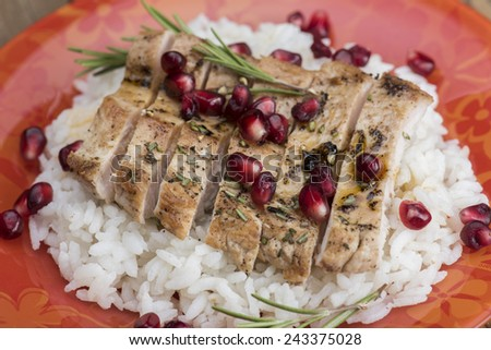 Grilled turkey with rice and pomegranate on an orange plate - stock photo