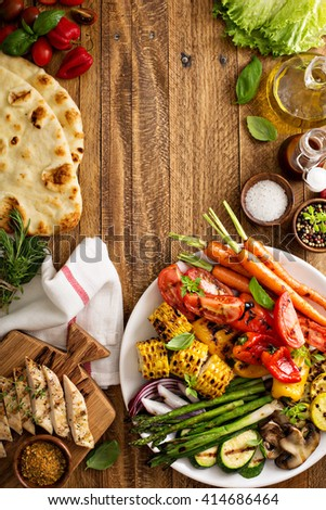Grilled vegetables and chicken on wooden table overhead shot - stock photo