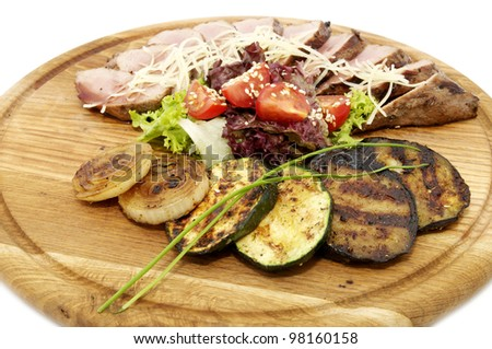 grilled vegetables and meat on a wooden platter - stock photo