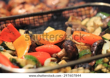 Grilled vegetables including zucchini, mushrooms, onions and peppers in a grill basket on a barbecue grill being cooked with chicken in background - stock photo