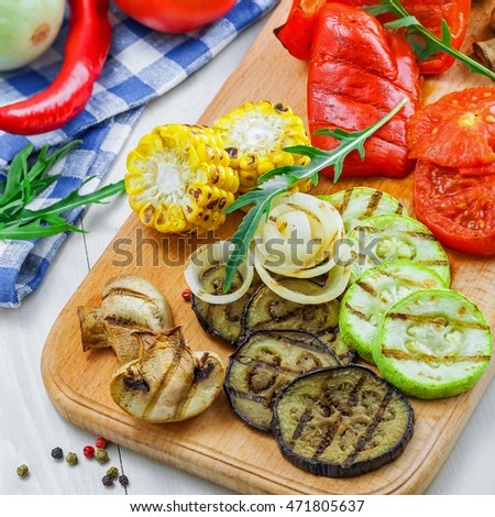 Grilled vegetables meal and ingredients on a table. Tomato, corn, eggplant, mushroom, bell pepper, marrow and onion prepared on a barbecue. Healthy food.