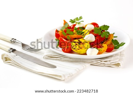 Grilled vegetables with mozzarella cheese. Cherry tomatoes, pepper, eggplant, zucchini served in white plate on white background with fresh herbs. - stock photo