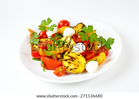Grilled vegetables with mozzarella cheese. Cherry tomatoes, pepper, eggplant, zucchini served with fresh herbs. - stock photo