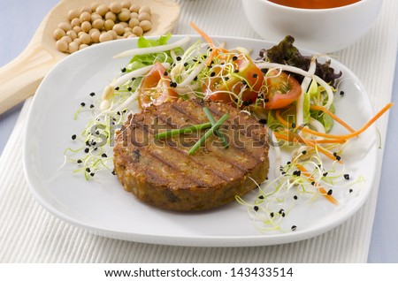 Grilled vegetarian tofu burger on a ceramic plate. Soy products. Focus on foreground. - stock photo