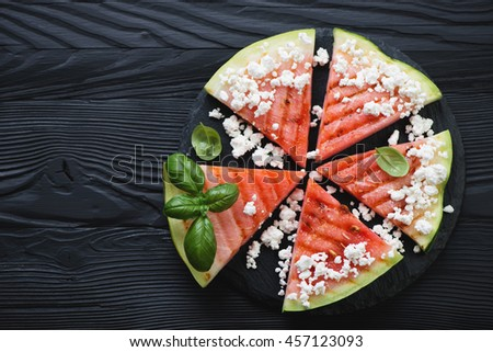 Grilled watermelon with cottage cheese on a black wooden surface, above view