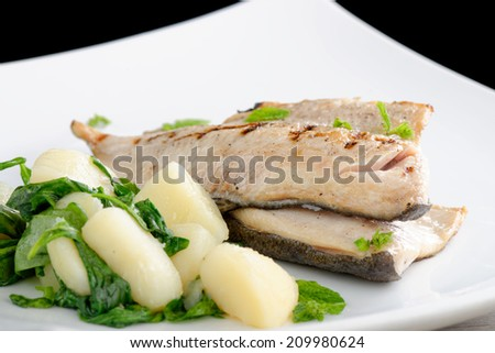 Grilled white fish fillets with potato and spinach  - stock photo