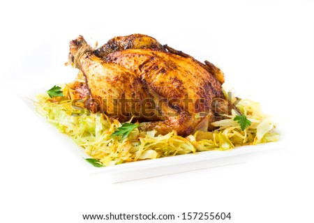 Grilled whole chicken with golden crust and garnish of stewed cabbage, isolated on white background - stock photo