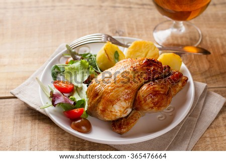Grilled whole small chicken with potatoes and beer, selective focus - stock photo