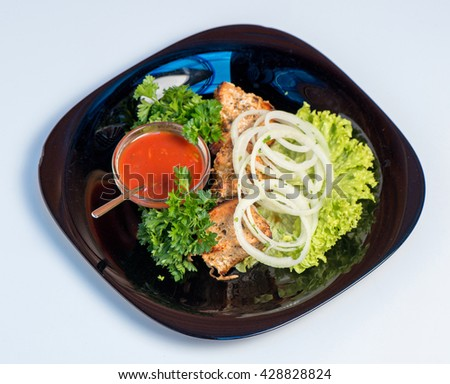 Grilled with herbs and salad leaves on a black plate on a white background