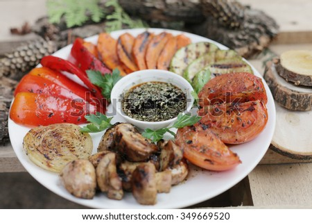grilled wooden vegetables. Grilled vegetables on the white plate. grilled vegetbles on the wooden background. Grilled onion. Grilled tomato. Grilled pepper. grilled mushrooms. Grilled vegetable marrow - stock photo