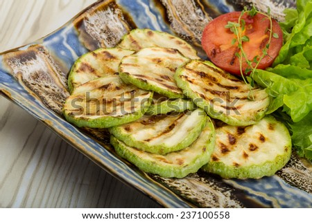 Grilled zucchini in the bowl with salad leaves - stock photo