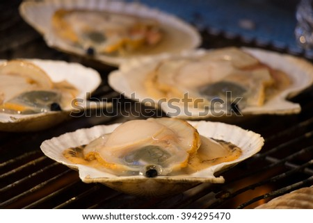 Grilling and burn oysters on flaming fire at Hokkaido morning market. Fresh and Delicious seafood breakfast. - stock photo
