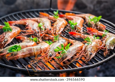 Grilling big prawns with lemon and parsley - stock photo