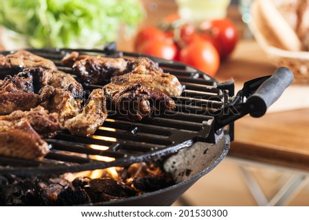 Grilling chicken wings on barbecue grill.