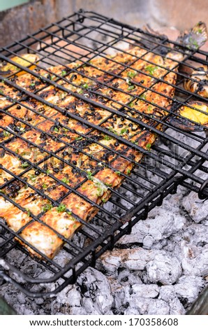 Grilling fish over charcoal, seafood barbeque  - stock photo