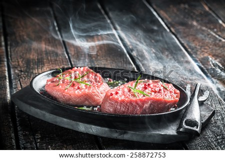 Grilling fresh piece of red meat with herbs