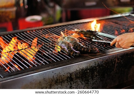 Grilling fresh shrimps on the flaming barbecue grill - stock photo