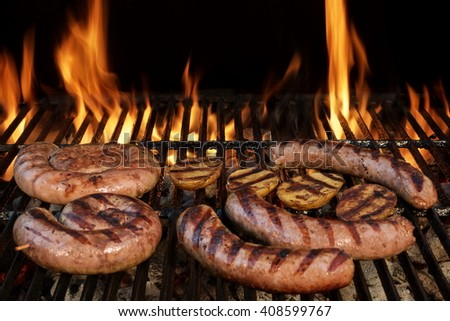 Grilling German Sausages On Hot Barbecue Charcoal Grill With Bright Flames On The Black Background. Cookout Food Concept.