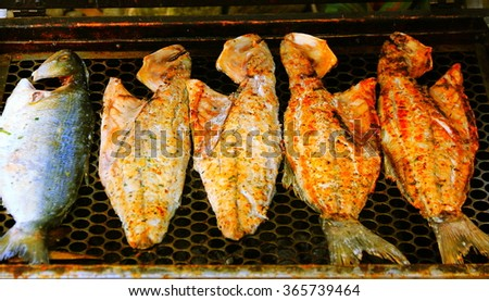 Grilling halves of bluefishes.    Grilling halves bluefish, with green spice