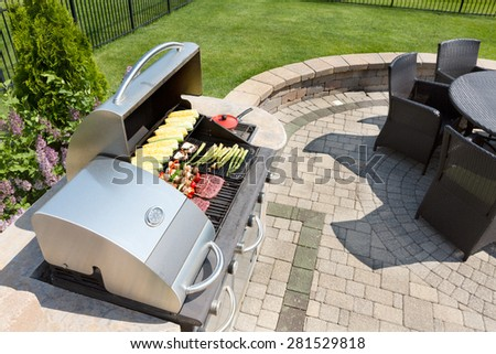 Grilling healthy food with corn, kebabs, meat and sausages on an outdoor gas barbecue on a luxury brick paved patio and summer kitchen in a neatly manicured back yard - stock photo