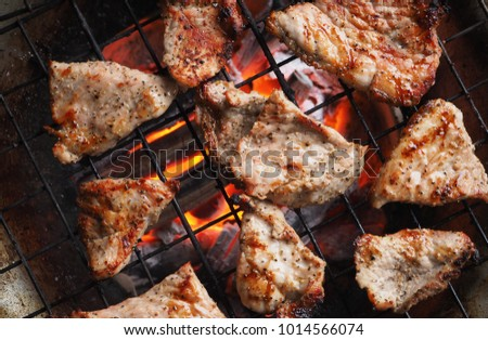Grilling pork meat on stove with black pepper