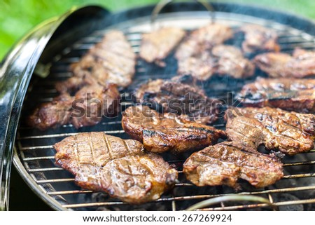 Grilling pork meat with barbecue stuff. Horizontal close up shot with a selective focus - stock photo