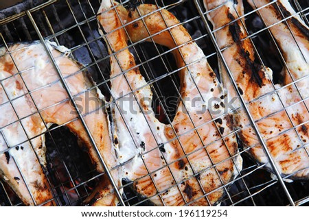 grilling salmon steak with milk cream in grid over barbecue