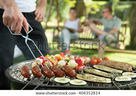 Grilling sausages and vegetables on bbq party - stock photo