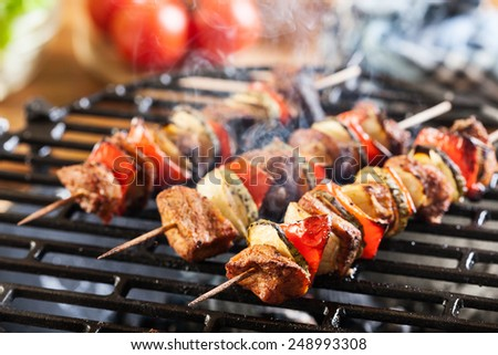 Grilling shashlik on barbecue grill. Selective focus - stock photo