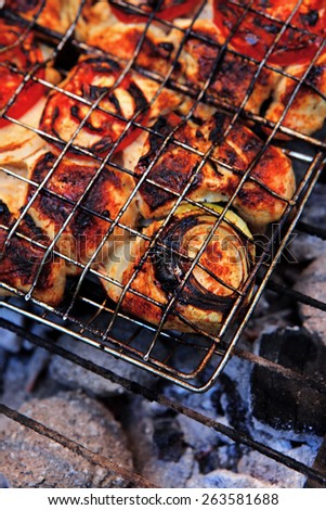 grilling spiced chicken in grid on charcoal bbq with tomatoes and vegetables - stock photo