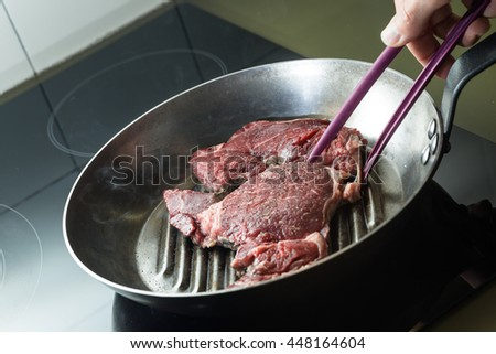 Grilling steak on grill pan. Beefsteak cooking on a kitchen. Fresh, delicious, spicy, juicy meat with copy space closeup.