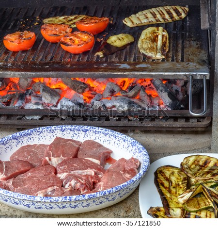 Grilling vegetables on barbecue, tomatoes, zucchini and eggplants, with a dish of beef meat waiting to be cooked