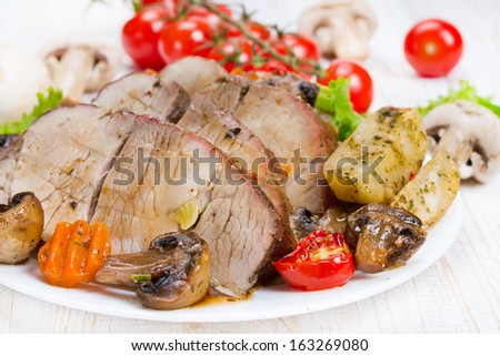 Grillrd meat with vegetables on a white plate