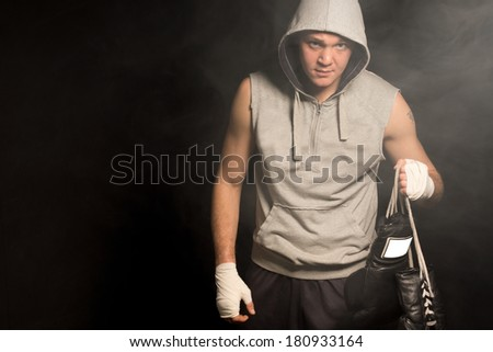 Grim looking boxer leaving a fight after a defeat as he carries his gloves by the laces and scowls at the camera from under his hoodie, with copyspace - stock photo
