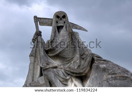Grim reaper Death personified as a skeleton with a cloak and scythe. This picture of weathered sculpture was taken in a French cemetery. This tombstone was built in memory of a sailer. - stock photo